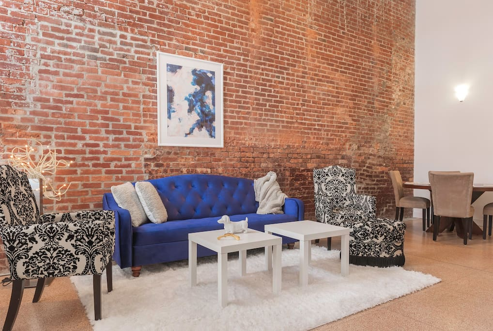 Dramatic brick wall shows off the cobalt velvet couch in the large living room.