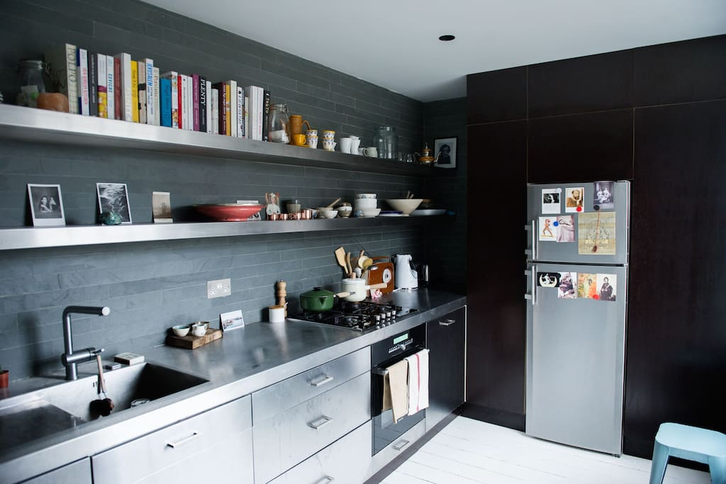 Cookbooks, stainless steel surfaces and breakfast stools.