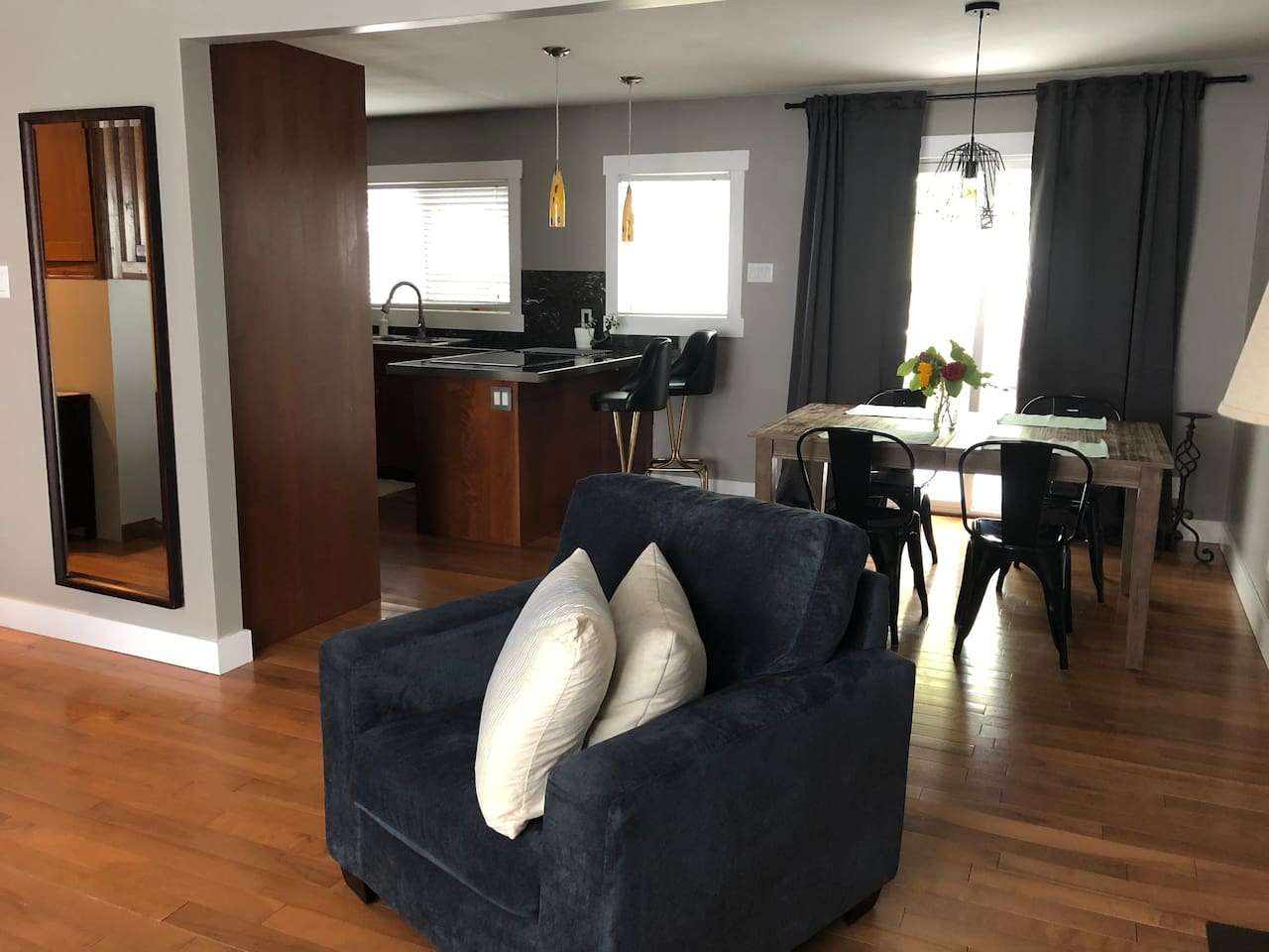 Open concept kitchen/ dining / living space. Modern furniture and updated appliances in the kitchen.
