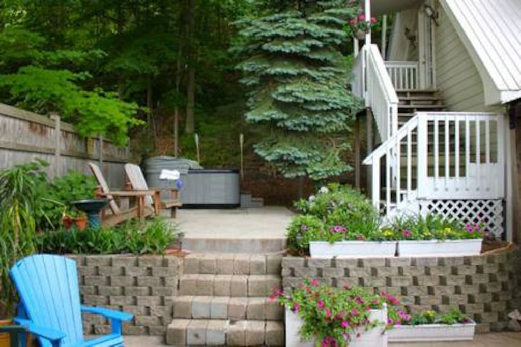 Inviting patio filled with flowers and plants - and a hot tub.