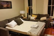 Comfortable queen sleeper sofa in living room with pillows, sheets and blankets to enable house to sleep six.