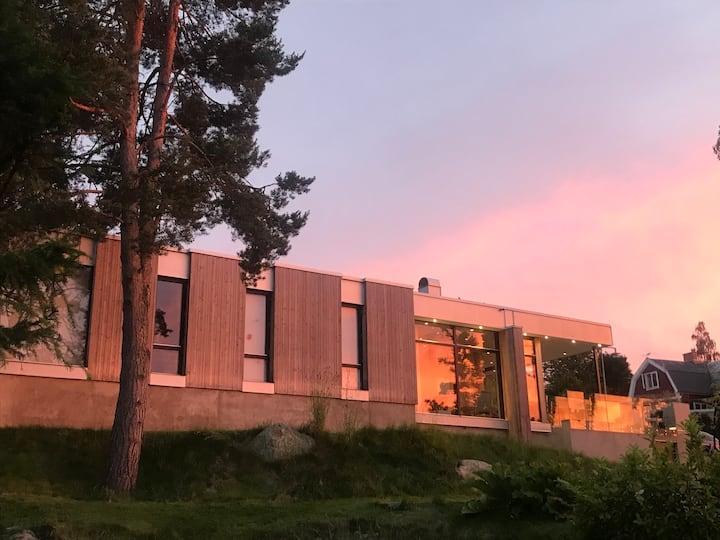 Arkitektritad villa i sommaridyll med sjöutsikt