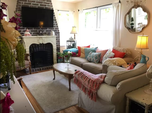 Cottage living room with fireplace, large flat screen HD TV, cable, and DVD player.