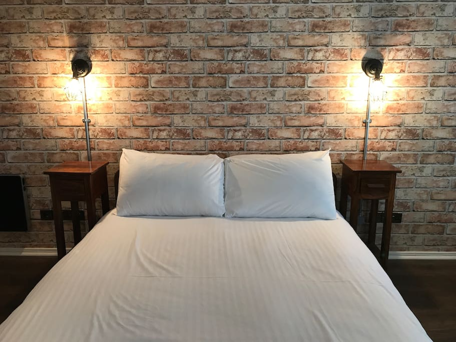 Super comfy king size bed with industrial bedside wall lamps