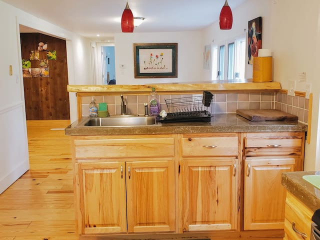 The bright kitchen has concrete counter tops, tile backsplash, and the basic appliances for cooking homemade meals.
