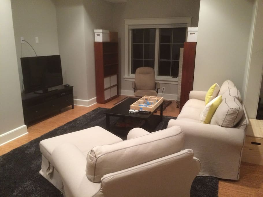 "47"" television, sofa and chair in living area"