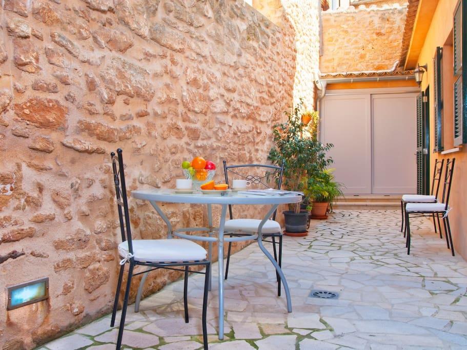 Zona de desayuno en el patio con mesa, sillas y hamacas