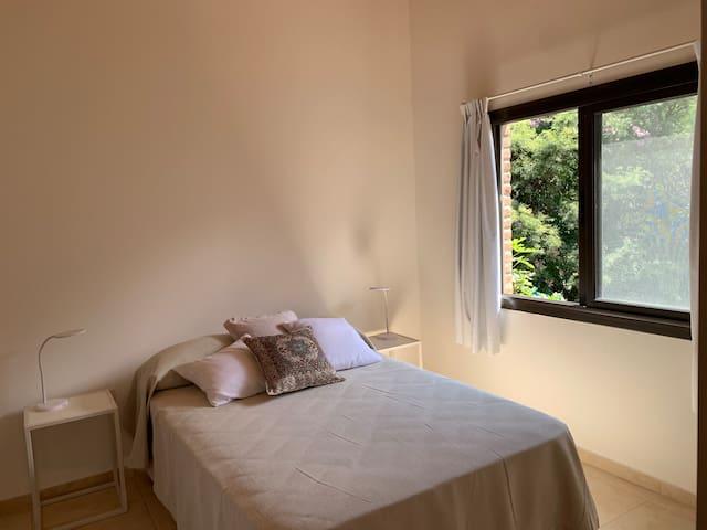 Dormitorio con sommier de 1,30 mts, T.V smart, placar abierto, y ventana con vista a la vegetacion.