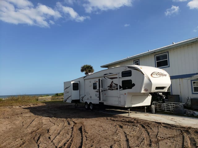 View of the RV from the neighbor's lot. The ocean & beach dunes are on the left.