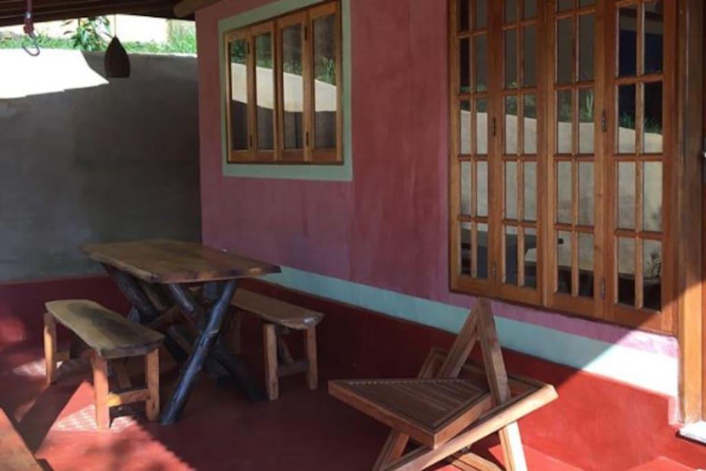 Varanda externa com mesa de jantar, cadeira e rede.