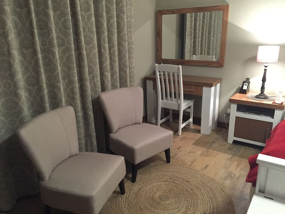 A spacious bedroom with comfortable seating and a workspace