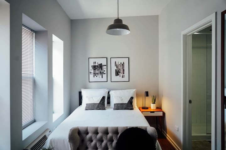 Comfortable queen sized bed with natural lighting in the bedroom