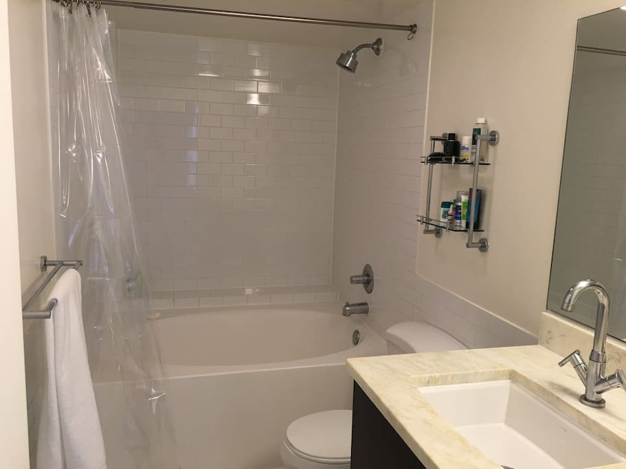 Shared bathroom and tub in unit.