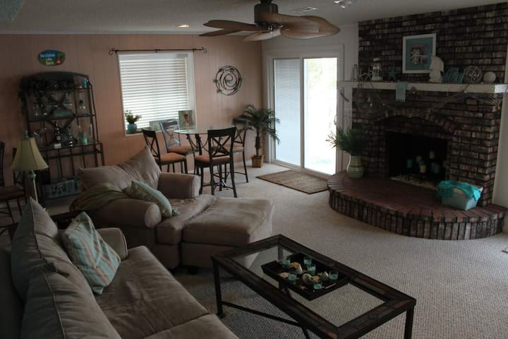 Living room with cute beach decor with two sliding glass doors to the outside patio and also open to the kitchen.
