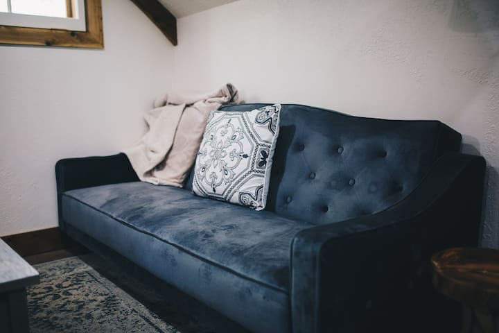 Velour couch and double bed.