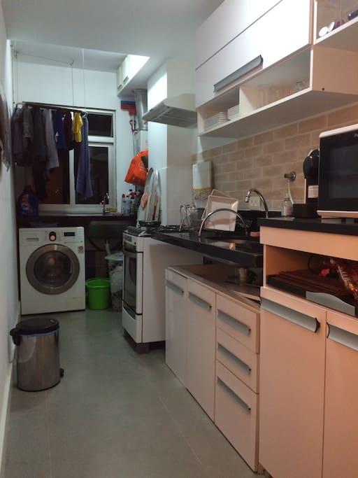 Área de serviço com tanque, varal, lavadora e secadora de roupas, anexa à cozinha, com forno convencional, fogão, forno de microondas e geladeira com freezer (este eletroeletrônico não aparece na foto).