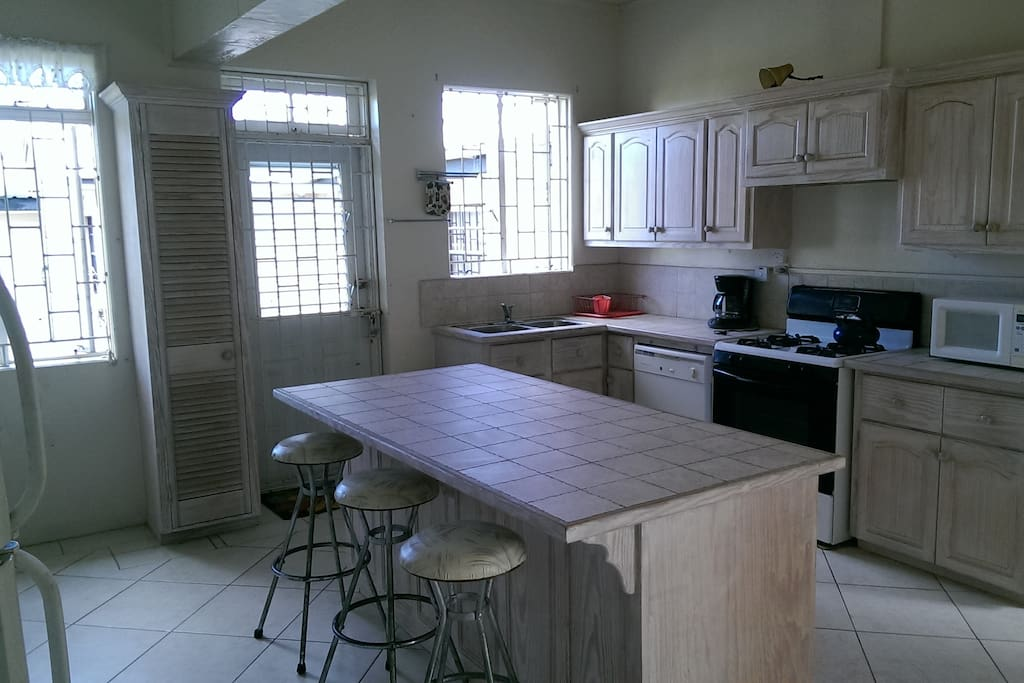 Enter into large eat in kitchen with stove, fridge, microwave, toaster, coffeemaker, cookware, dishes and silverware.  Kitchen also has exit to backyard and laundryroom.