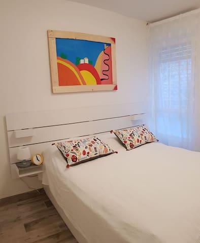 The main Bedroom.  Queen size bed, original art and plenty of natural light