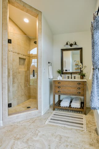 Farmhouse vanity with marble top, custom floor to ceiling tile shower