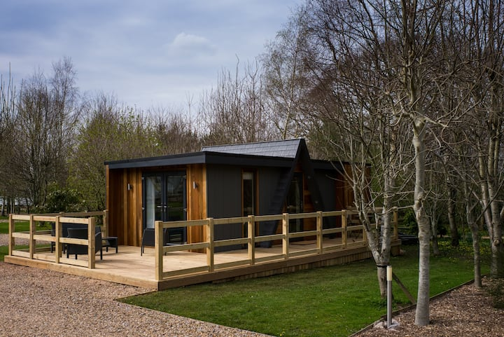 A contemporary lodge at the edge of a small wood
