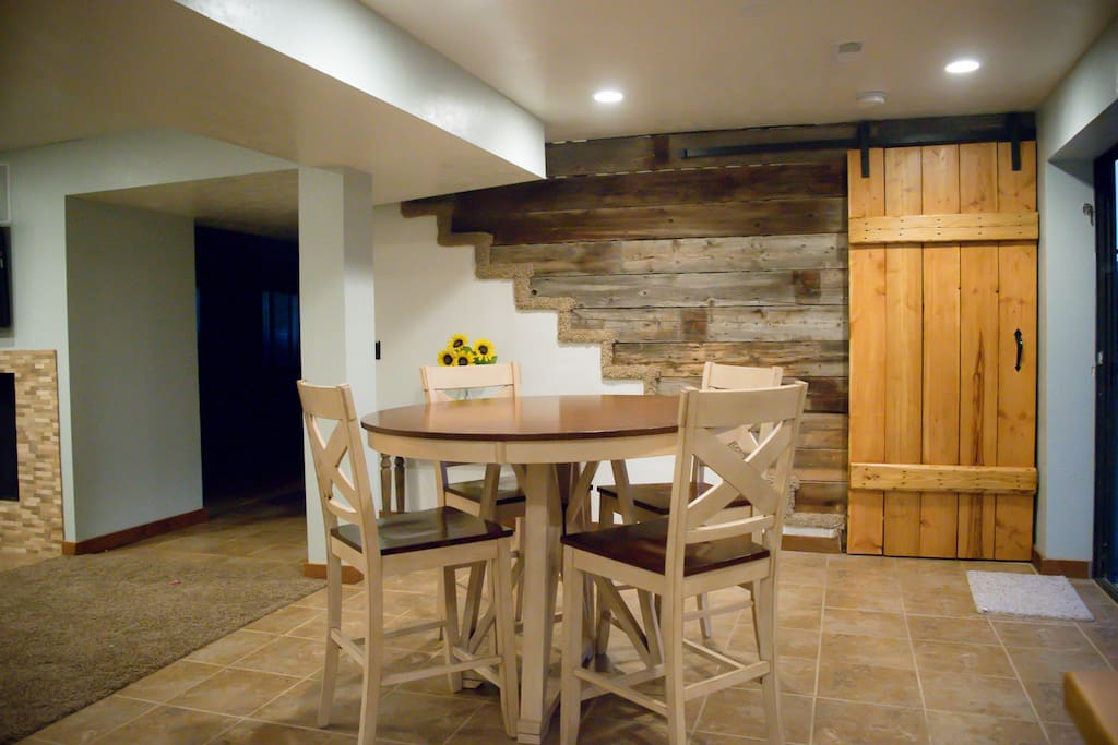 Enjoy your meals in the dining space. Barn wood ship lap with a sliding barn door in the background.