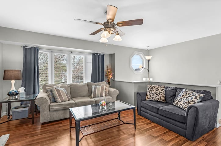 Living room with wood burning fire place, large beautiful bay window with the perfect amount of natural light, smart TV, pull out bed from couch, love seat and sitting chair. Perfect place to hang out with friends or relaxation