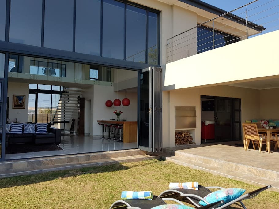 River view of house with stack doors opening out to a swimming pool, entertainment area with outdoor braai and pizza oven
