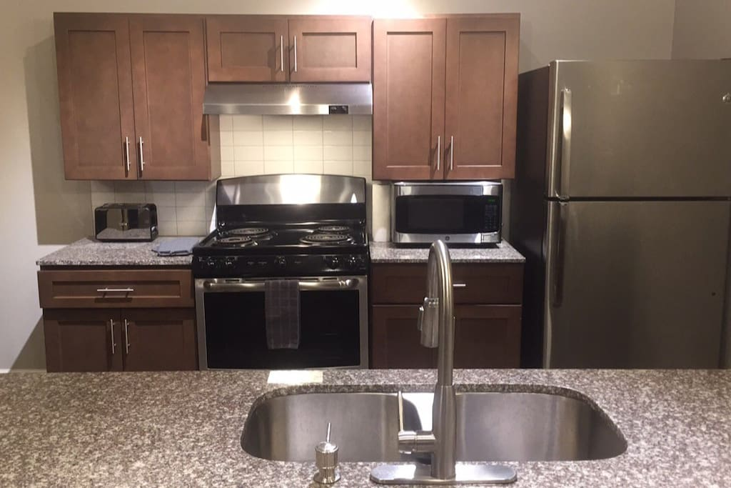 Full size Kitchen with stainless steel appliances, coffee maker, and toaster.
