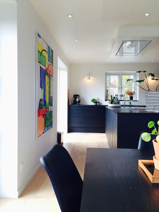 Stort moderne køkkenalrum med intelligent induktionskogeplade, ovn (med rotisserie), microbølgeovn, quooker og espressomaskine samt almindelig kaffemaskine