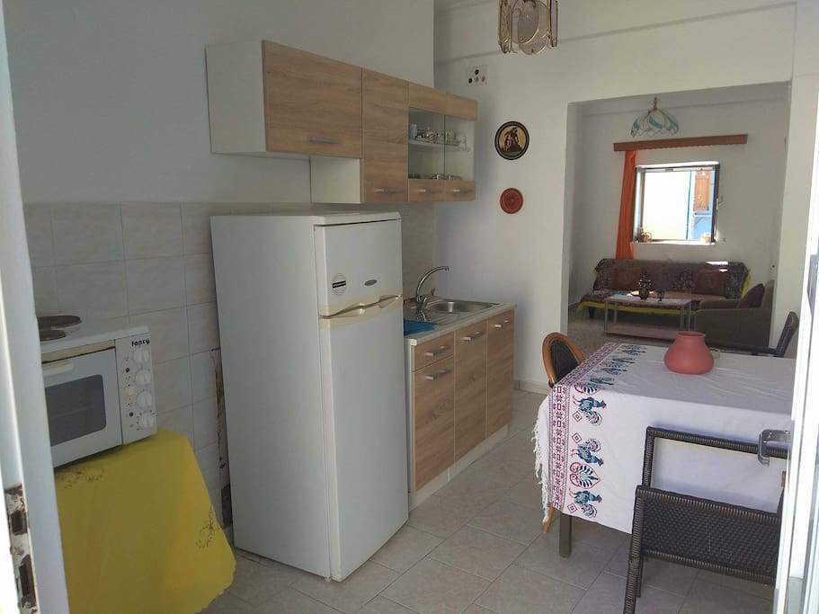 The kitchen that includes a fridge a cook oven if you like to cook and a table with chairs.
