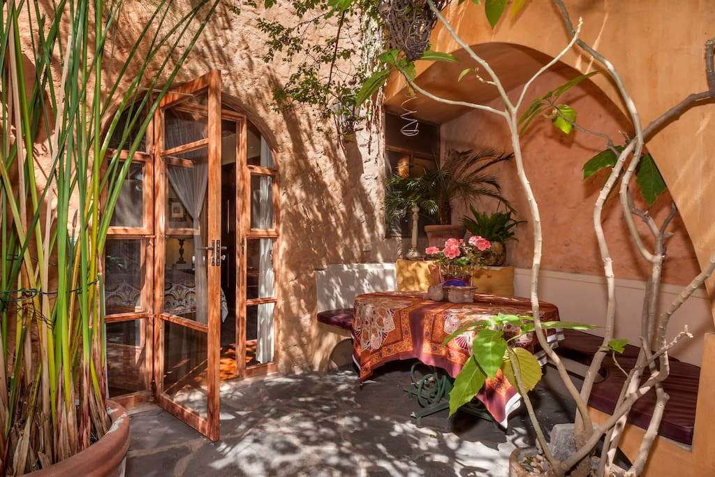 Entrance to casita; outdoor dining and banquette with organic kumquat and pomegranate trees.