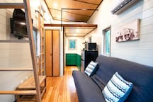 This modern tiny home lives large with two lofts: one queen sized bed, one twin. The futon downstairs folds out into a double bed. Featuring hand-built woodworking throughout.