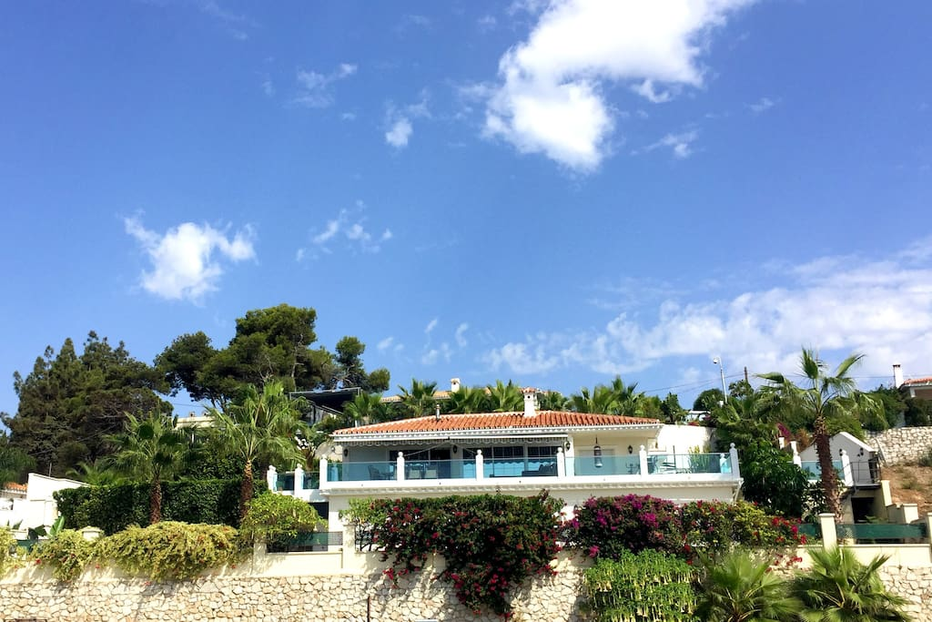 The villa is distributed over two floors and surrounded by gardens and terraces.
