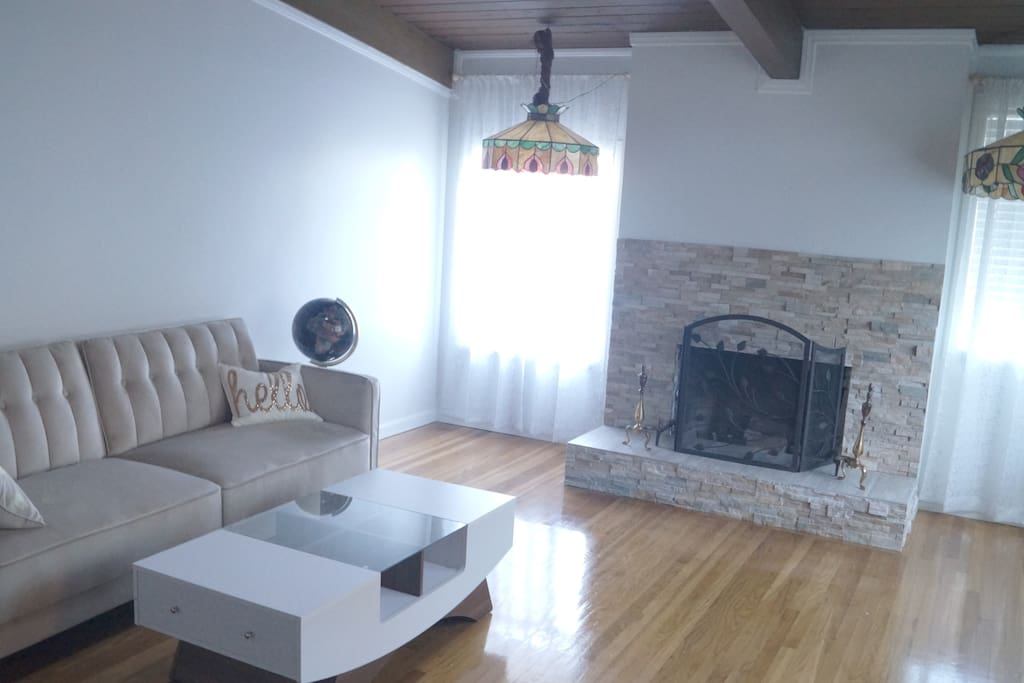 spacious entrance room with fireplace, expandable sofa and skylight