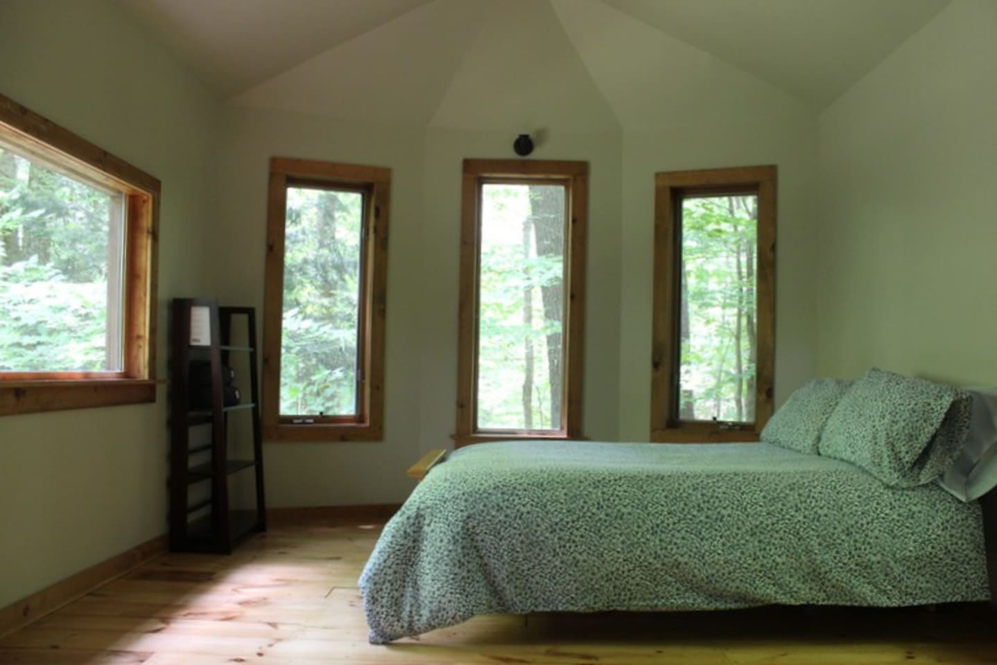 Comfortable bed with warm bedding and surrounded by views of the forest.