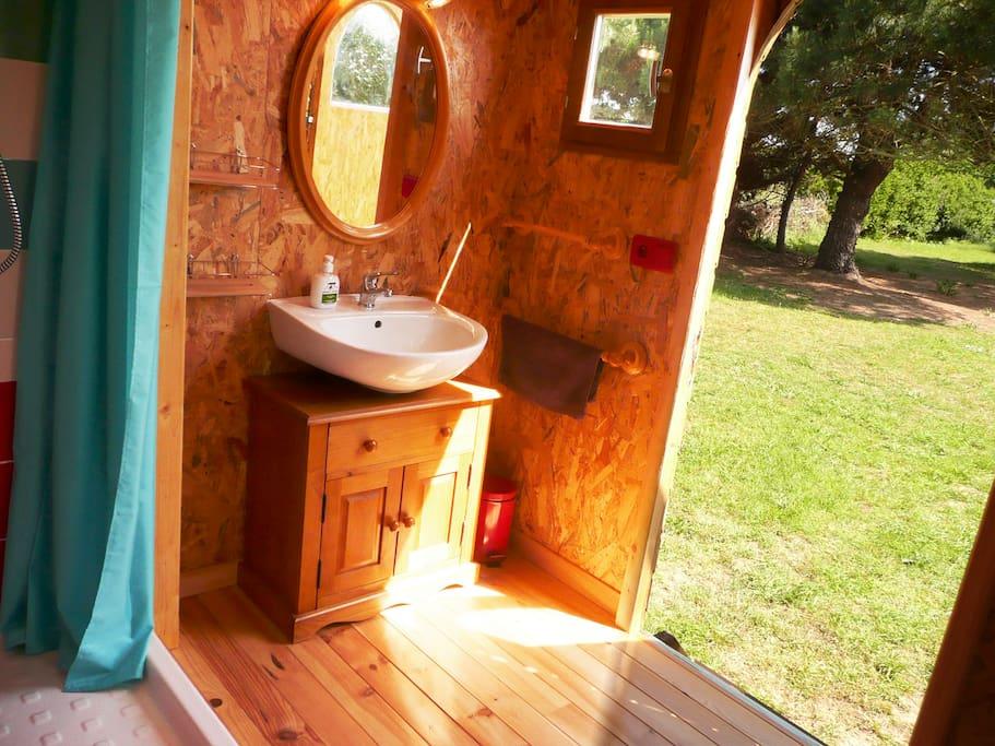 Vue depuis la roulotte - salle de bain. Spacieuse et confortable, la salle de bain abrite également les toilettes et la machine à laver.