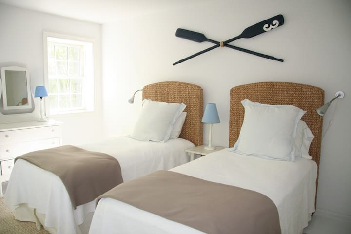 Upstairs bedroom - twin beds, a large soft rug on painted floorboards and plenty of shelving/drawers and hanging space