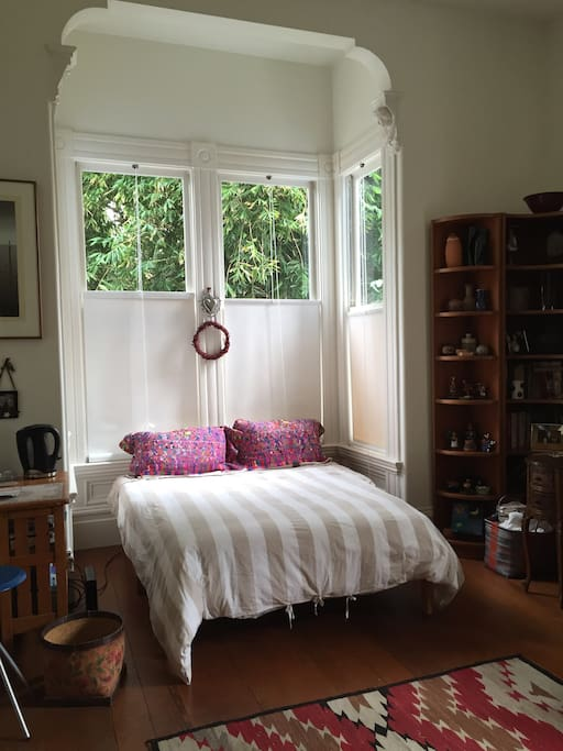 The room, surrounded by lots of books, and plenty of greenery out the window.