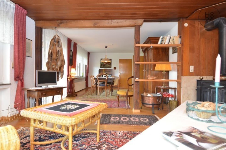 Großzügiges Wohn- und Esszimmer mit Fernseher und gemütlichen Sitzgelegenheiten.