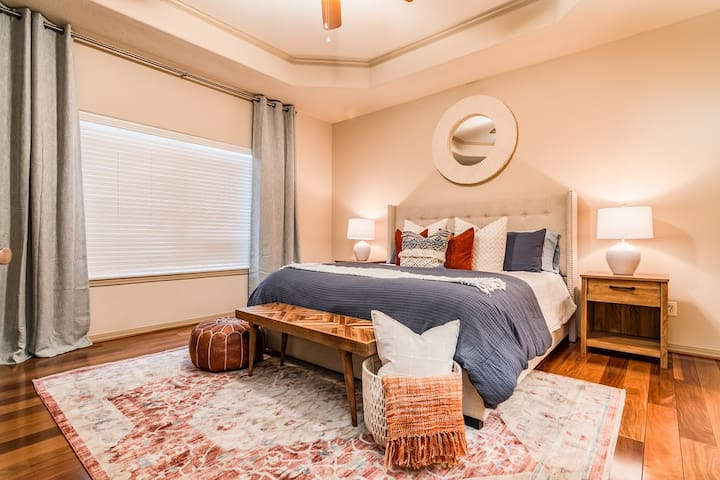 The master bedroom features a king size upholstered bed and lots of extra space!