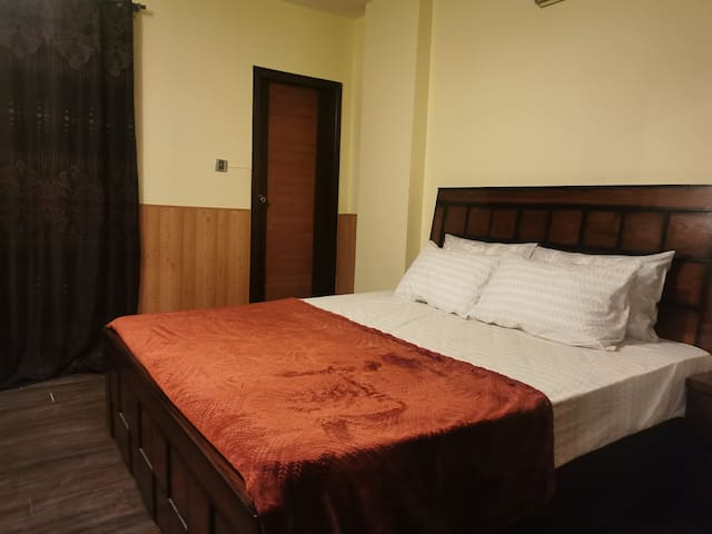 Bedroom with king size bed and inverter aircon. Access to balcony with beautiful views of Margalla hills.