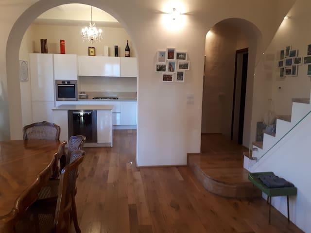 Cucina, sala da pranzo e soggiorno open space. Scala che sale al piano superiore