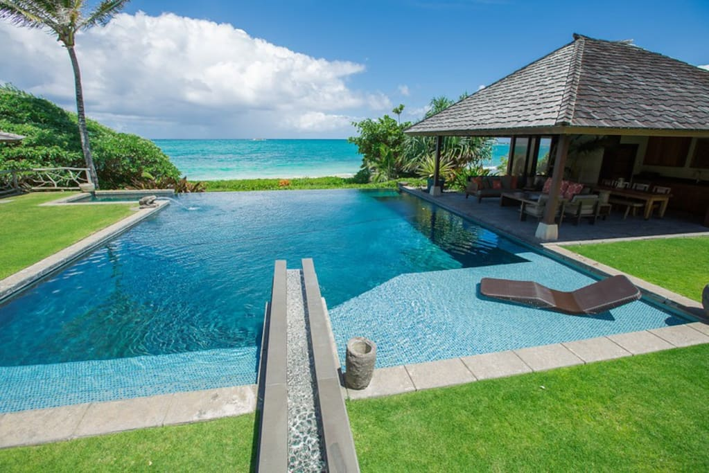 Infinity pool with water features and views of the beach