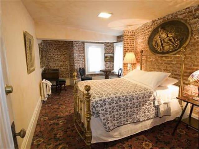 En suite bedroom with a full bed and windows overlooking Steiner Street.