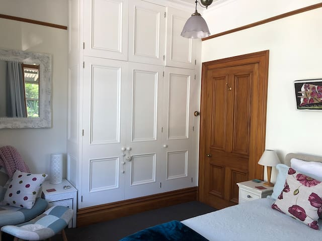 Main bedroom with large wardrobe. Corner seat and footstool.