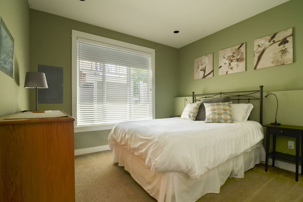 Comfy bed with down comforter.  Blackout shade behind wood blinds.
