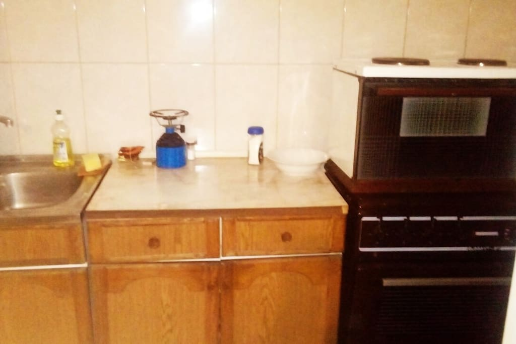 Kitchen fully equipped with fridge, stove and other standard white goods.