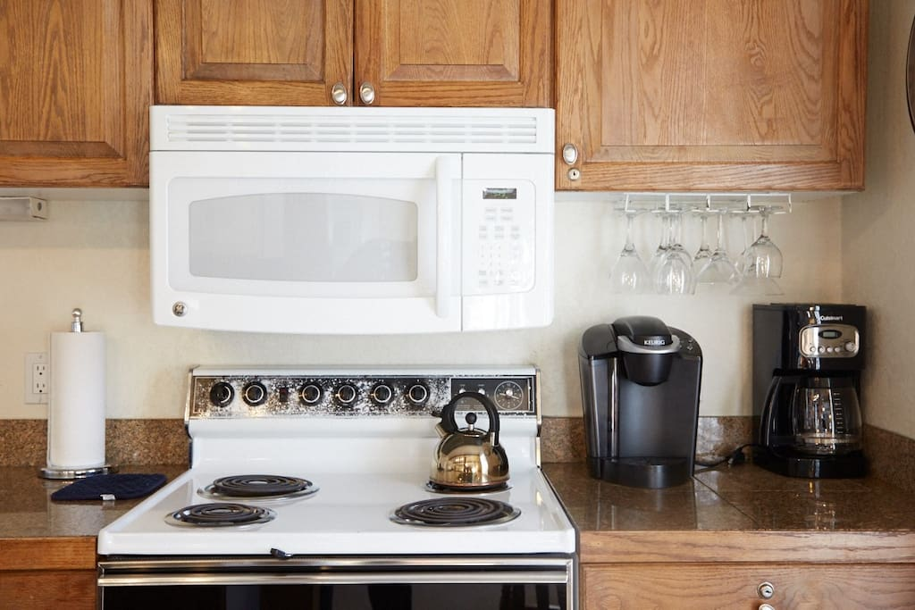 A modern microwave and 4 burner oven are conveniently located together.