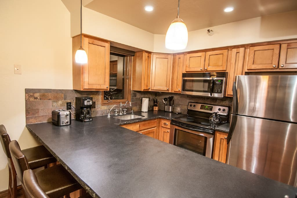 Fully stocked kitchen with counter top seating for three people