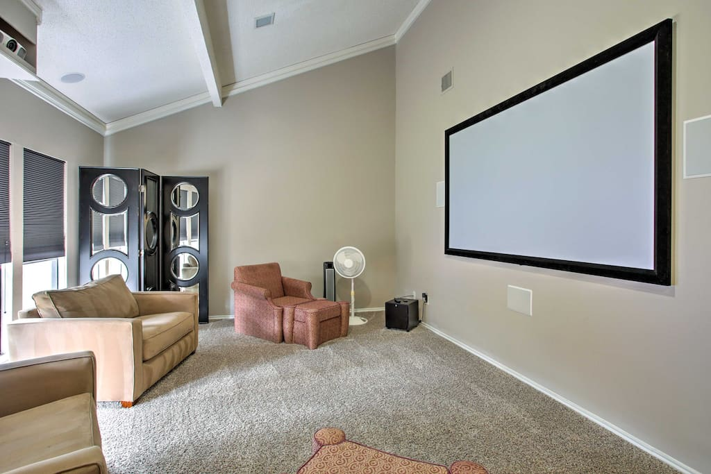 Relax and watch your favorite movies or TV shows on the 106-inch projector screen in the media room.